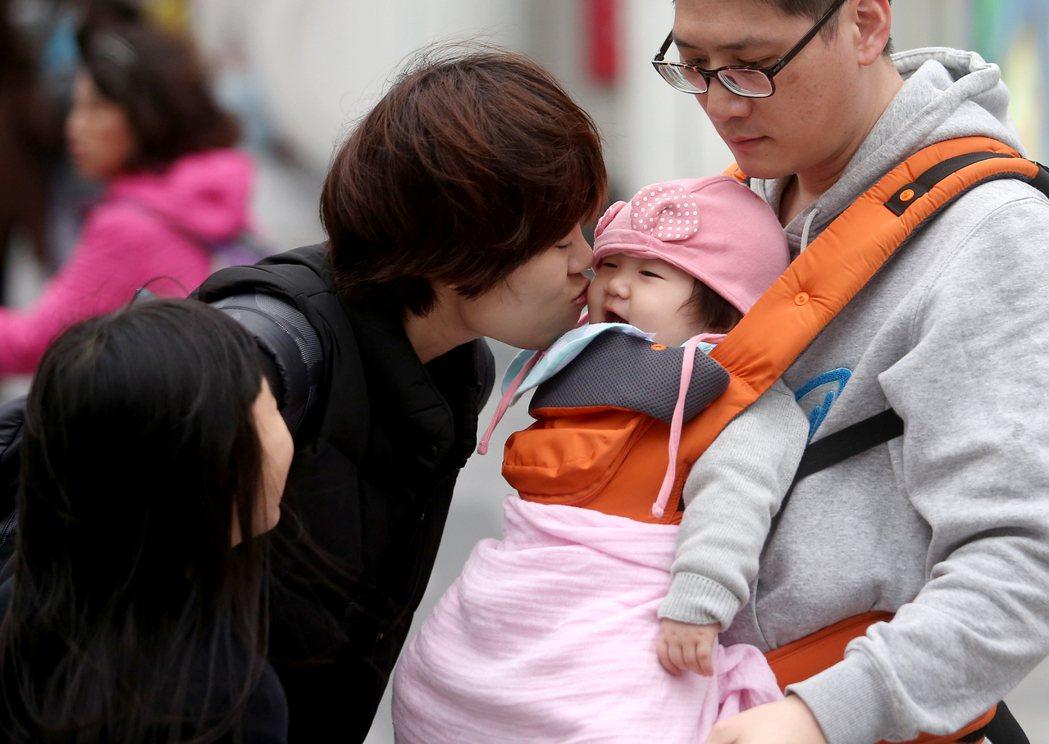 台北市5日受到鋒面通過影響,傍晚氣溫微降飄起細雨,一對父母替小孩戴上帽子遮擋涼風...