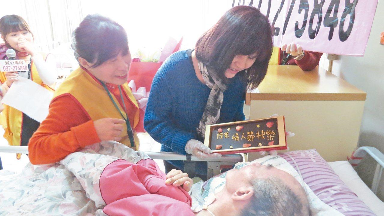 昨天是西洋情人節,苗栗市婦人李秀英(圖右)昨天在病床旁大聲祝福植物人丈夫阿光「情...