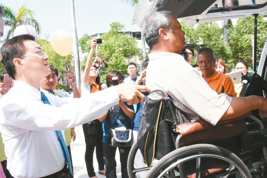 彰化縣府常接獲中小企業捐贈小型復康巴士,縣長魏明谷(左)在捐贈儀式中,推身障者上...