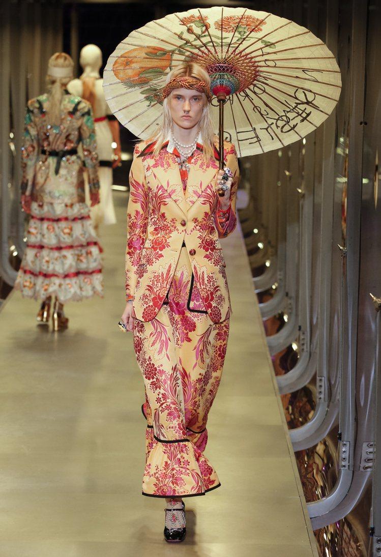 撐著東方風格紙傘的模特頭上繫著西方風格的頭巾。圖/Gucci提供