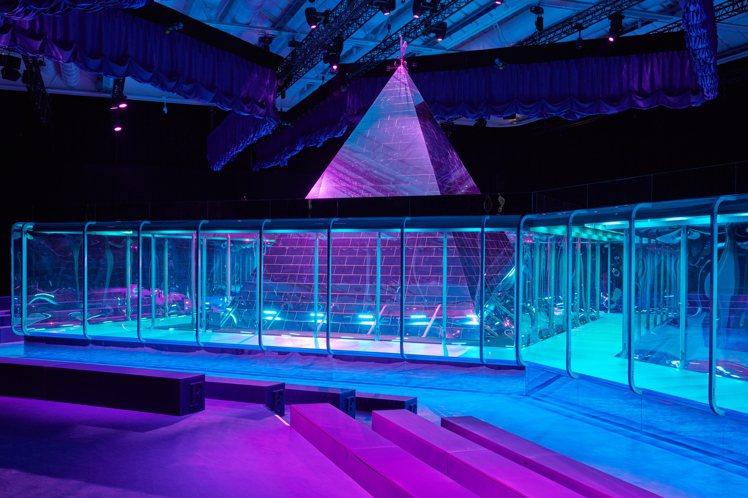 「煉金師的秘境」為本季主題,金字塔聳立在充滿神秘紫色霓虹的服裝秀場中心。圖/Gu...