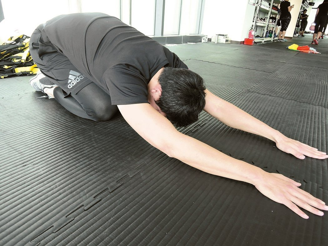 背部伸展動作臀部坐於腳跟上,上半身呈趴姿。 記者陳珮琦/攝影