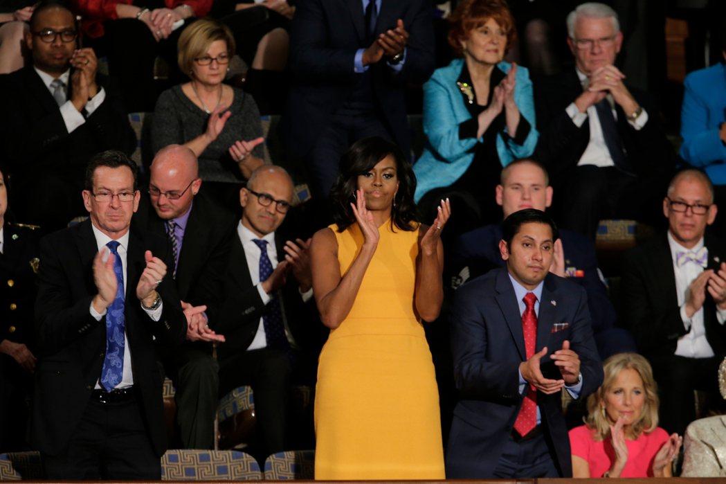 蜜雪兒‧歐巴馬(中)去年出席前總統歐巴馬最後一次國情咨文演說,選穿的黃色禮服露出...