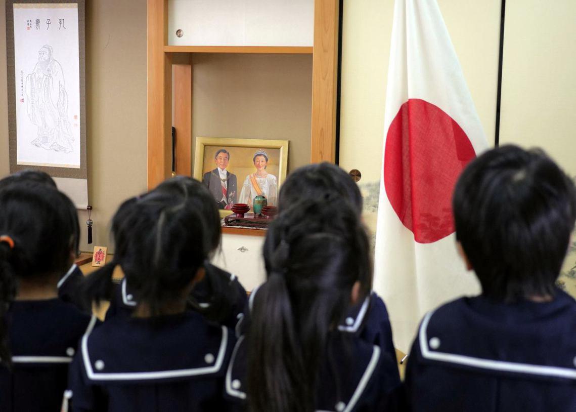 塚本幼稚園的學童,正注視著天皇夫婦像,左側還有一幅孔子像,象徵在幼稚園中實施的傳...