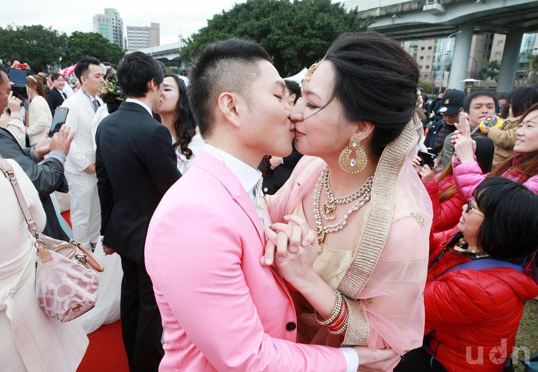台北市第214場的聯合婚禮在華山大草原舉行,新人們深情擁吻十分浪漫。記者黃義書/...