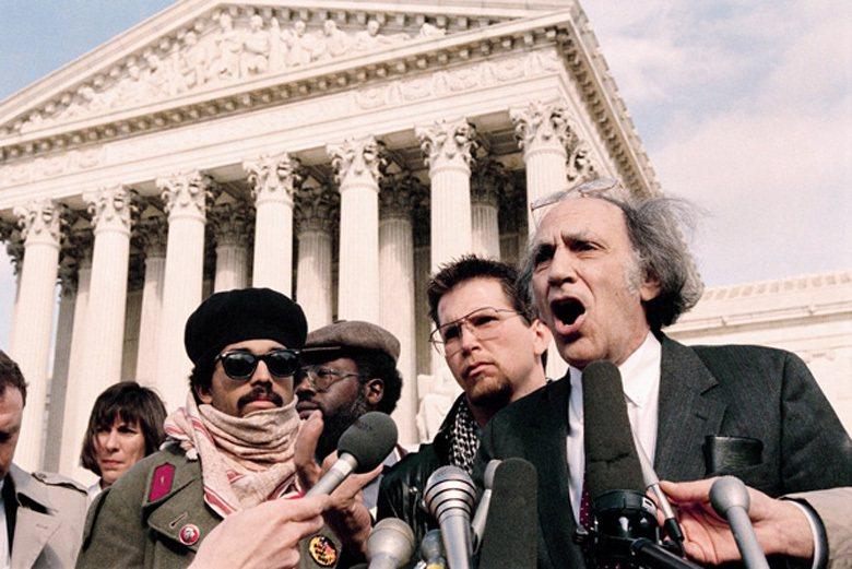 強森於1984年在大庭廣眾之下燒毀國旗,抗議著雷根總統過去四年的政策。爾後強森遭檢察官起訴。右二為強森,發言者為他的辯護律師。 圖/美聯社