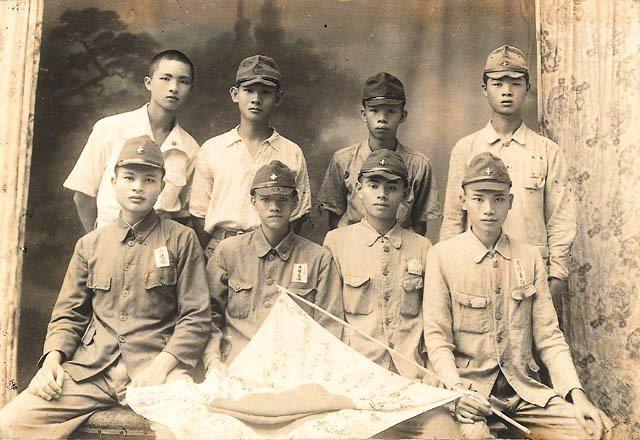 出征前的臺灣兵於攝影社內合影,前排右者手持日本軍旗。