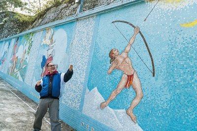談起費時15年才完成的馬賽克拼貼壁畫,丁松青俏皮地模仿泰雅戰士射太陽,表示遇到困...