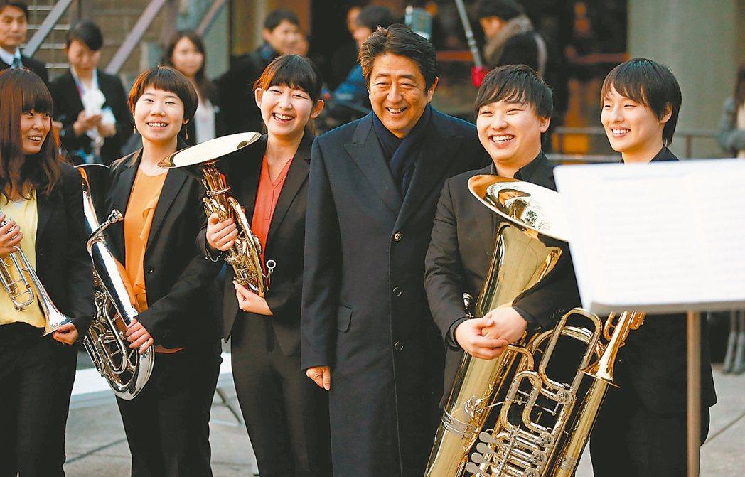 日本首相安倍晉三(右三)上月24日「超五」在東京聽音樂會,並與樂隊成員合影留念。...