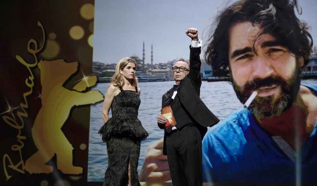 柏林電影節主席戴特柯斯利克(Dieter Kosslick)在典禮上高舉左手,聲...