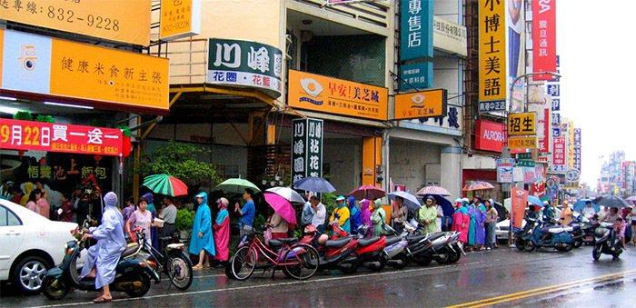 東港鎮一家便當店昨天開幕,打出「買一送一」促銷,吸引大批民眾冒雨排隊搶購,隊伍綿...