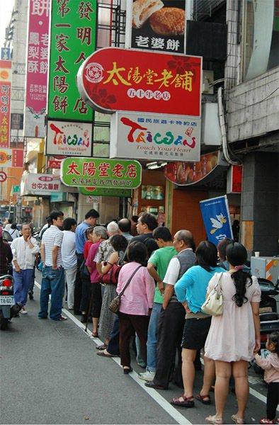 台中市特色商圈太陽餅文化日,店家推出「買一送一」優惠,吸引排隊搶購人潮。 圖片來...