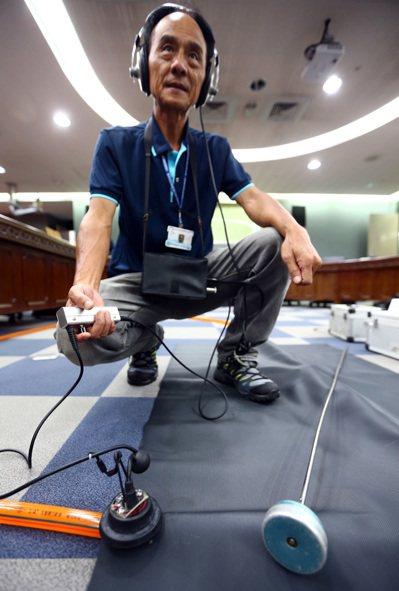 台北自來水公司展示用來抓漏的電子式測漏器(身上裝備)和聽音棒(前右)。 記者杜建...