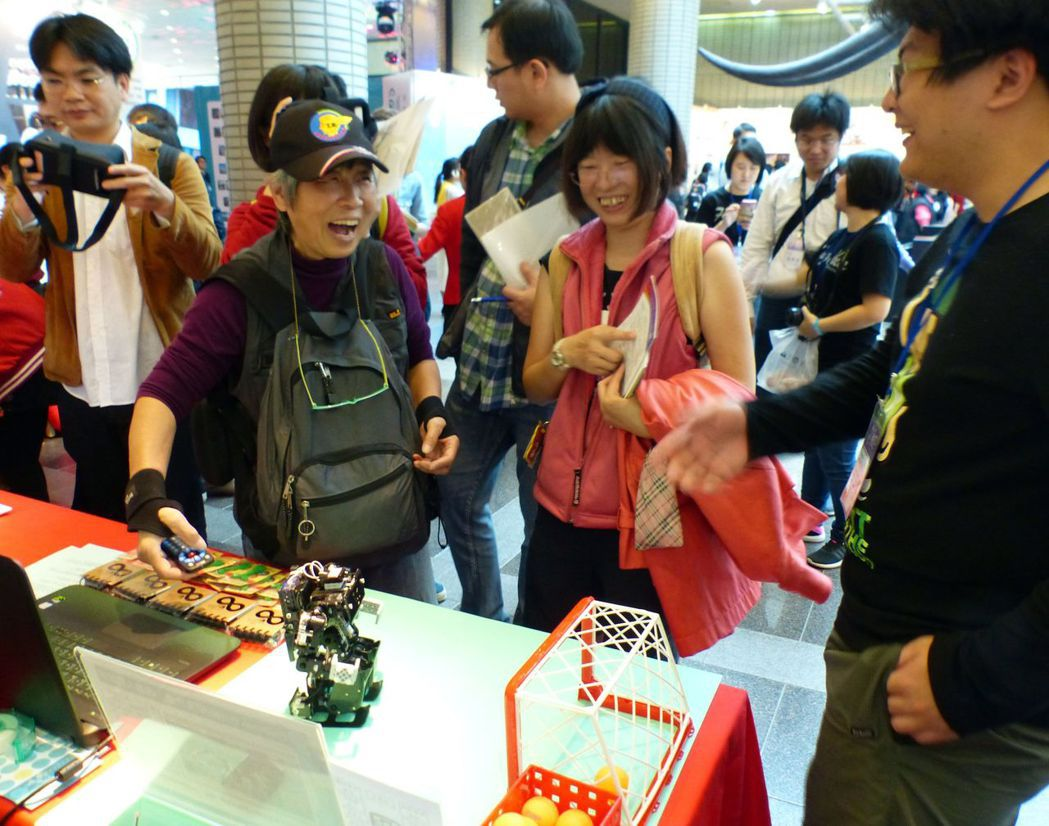 一名阿嬤用搖控器操縱逢甲大學學生設計的機器人,看到機器人把足球踢進得分,開心不已...