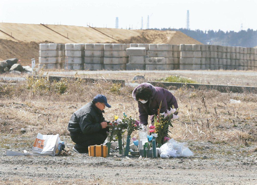 十一日是日本三一一大地震六周年,一對夫婦在福島縣浪江町準備花束,祭拜死於震災的女...