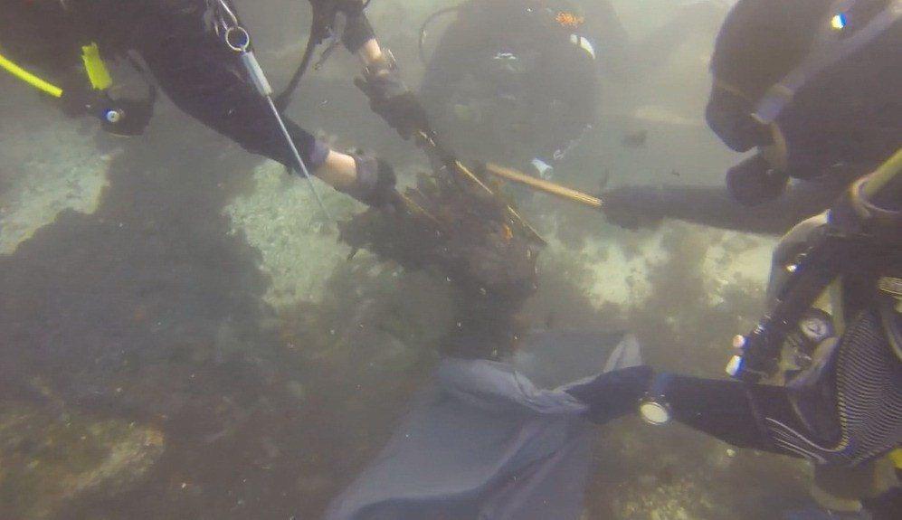 潛水志工下海以小木棒捲動、切割方式,清除覆蓋在海藻床上的油汙。 圖/翻攝自綠島飛...