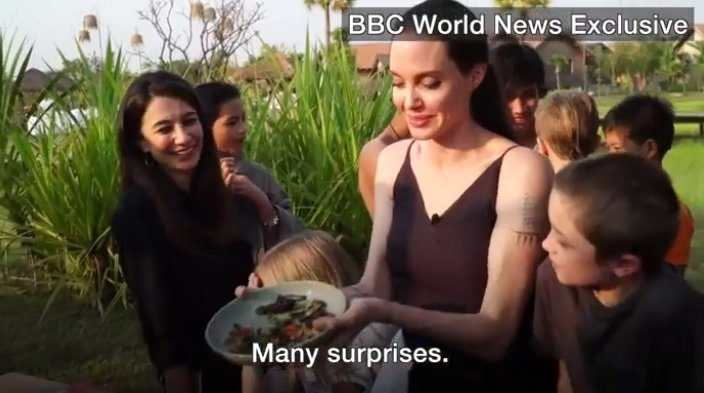 裘莉帶著幾個孩子在柬埔寨嘗試蟲蟲大餐時,也是穿了件絲質黑色洋裝。圖/摘自BBC官...