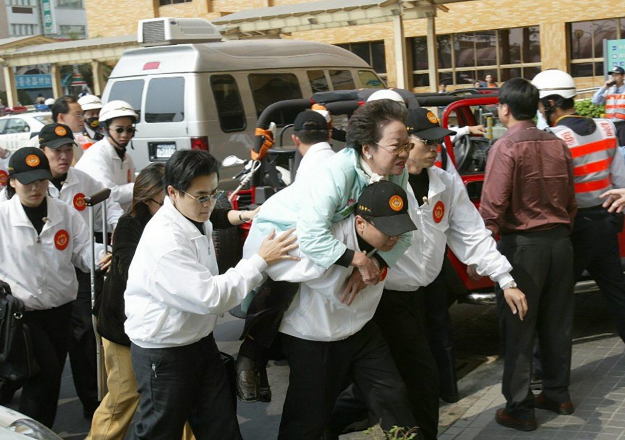 2004年三一九槍擊案發生後,呂秀蓮副總統由隨扈背著進入奇美醫院情形。照片與本新...