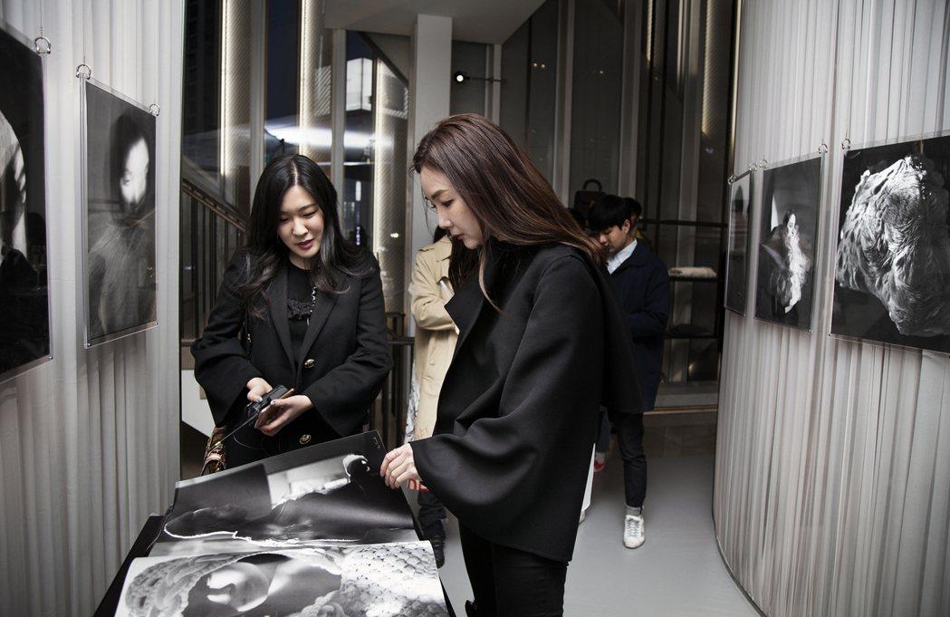 崔智友正專注瀏覽工坊訂製披肩的資料。圖/BURBERRY提供