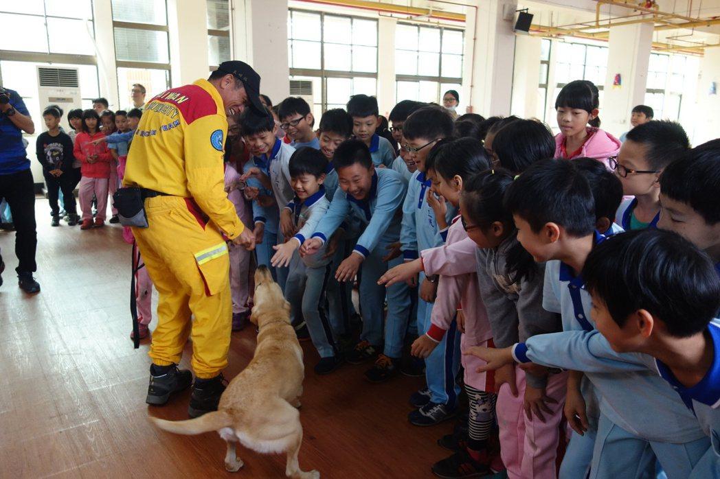 學童們跟培訓中的搜救犬貝斯互動,超開心,大家都伸手想要摸摸搜救犬。 記者劉星君/...