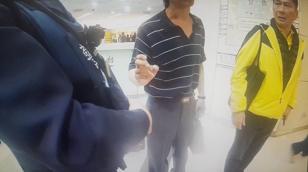 路人甲(穿條紋衣者)跟警察嗆說,「你們這樣做是不行的,是違憲的」。 圖/記者李奕...