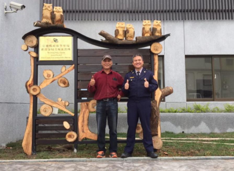 美城派出所所長林世光(右)請來擅長木雕的友人陳建造(左),在派出所前增加可愛的木...