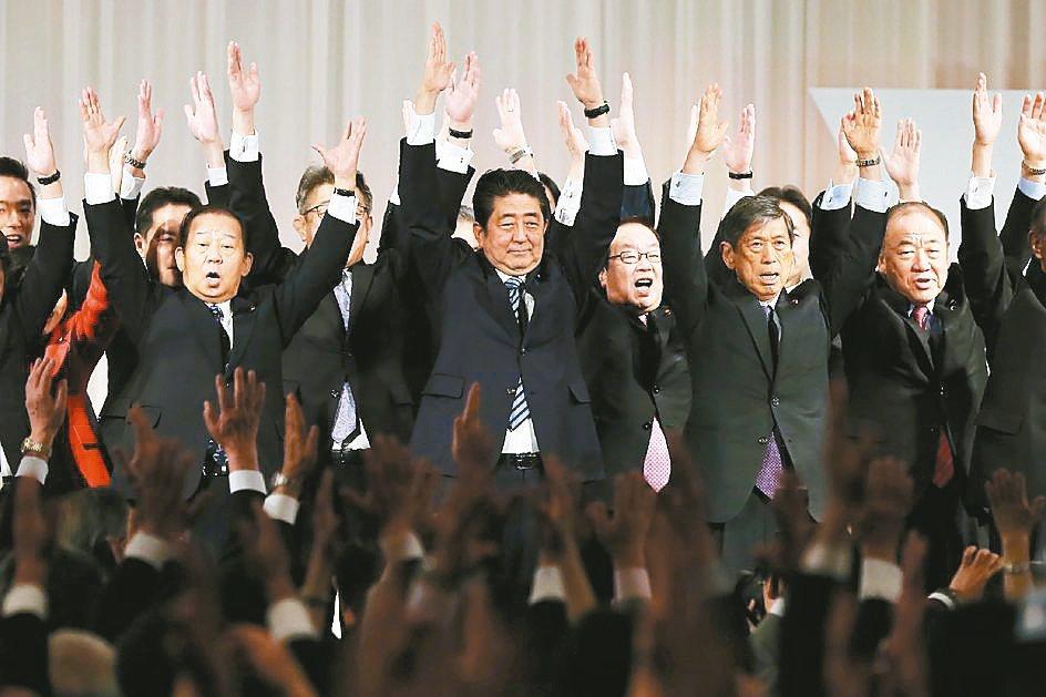 日本首相安倍晉三(中)5日在自民黨大會上,與黨員高舉雙手歡呼。 法新社