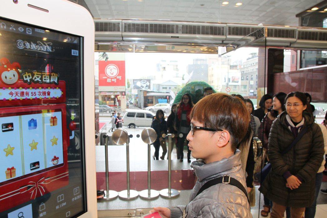 中友百貨昨一早就有消費者大排長龍,玩拉霸並試用手機版網購平台。記者黃寅/攝影