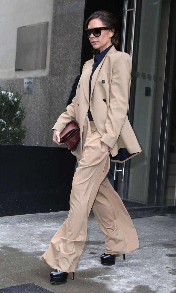 維多利亞貝克漢身穿卡其色寬版西裝套裝,長版外套搭配寬褲,走起路來有裙裝的飄逸又有...