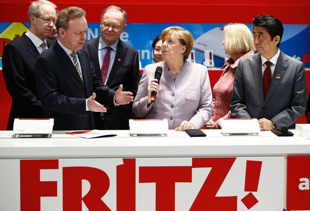 德國總理梅克爾(中)20日參觀漢諾威數位電子展,右為日相安倍晉三。(法新社)