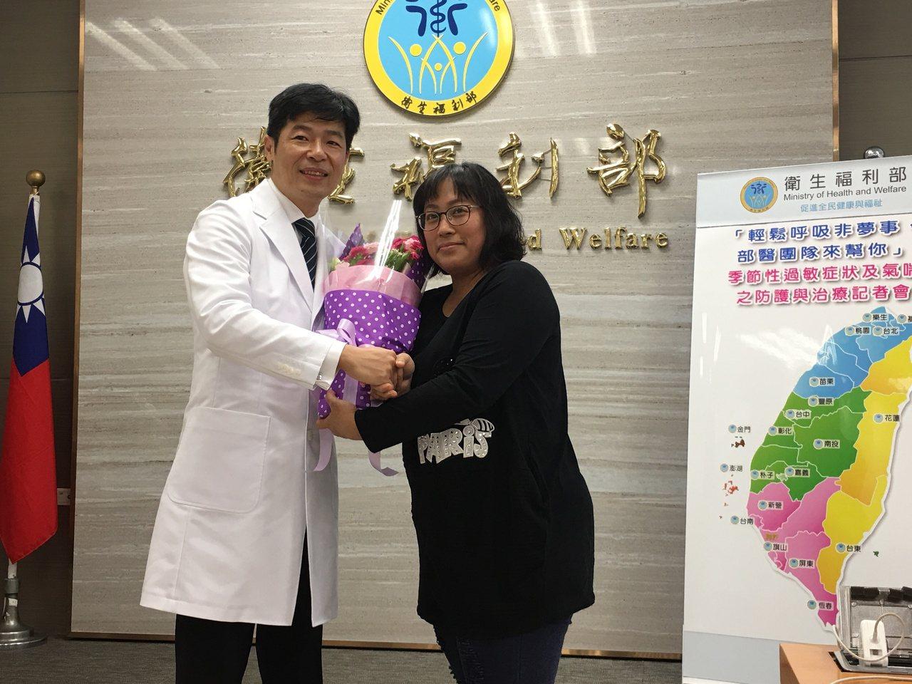 過敏性皮膚炎的馮太太(右)送上花束,感謝樂生療養院中醫科主任徐蔚泓(左)的治療。...