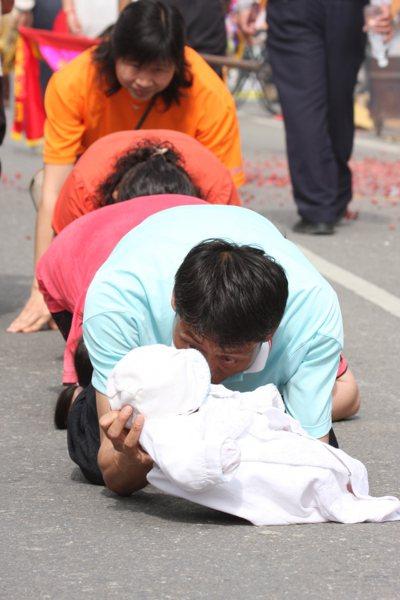 一名父親抱嬰兒等著鑽轎腳,跪在地時仍緊盯著孩子,慈愛之情不言可喻。 圖/本報資料...