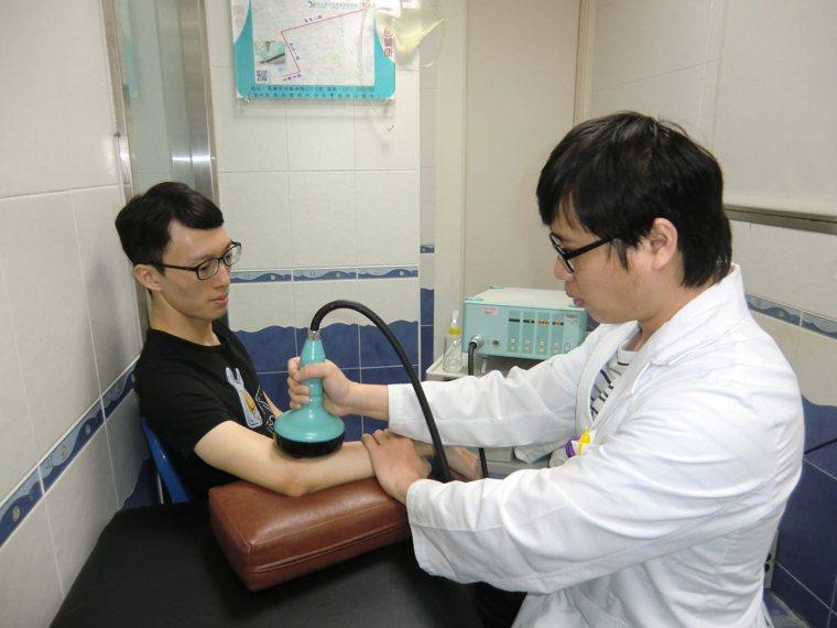 「活力得中山脊椎外科醫院」復健室主任尤政中(右)說,利用震波治癒網球肘,快速有效...