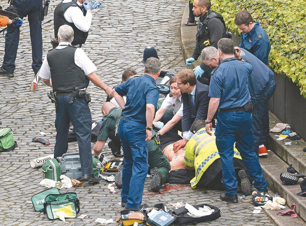 英國保守黨國會議員也是外交部次長的艾伍德(中)奮力搶救遇刺的警官,可惜仍回天乏術...