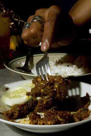 一名顧客在印尼日惹的餐廳吃狗肉飯。 (路透)