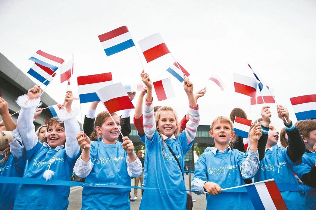 孩子們揮舞荷蘭與波蘭國旗,歡迎荷蘭國家足球隊到訪。 法新社