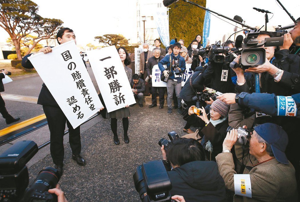 福島災民律師團17日在法院前高舉勝訴標語牌,歡迎法院判決政府與東電必須共同承擔核...