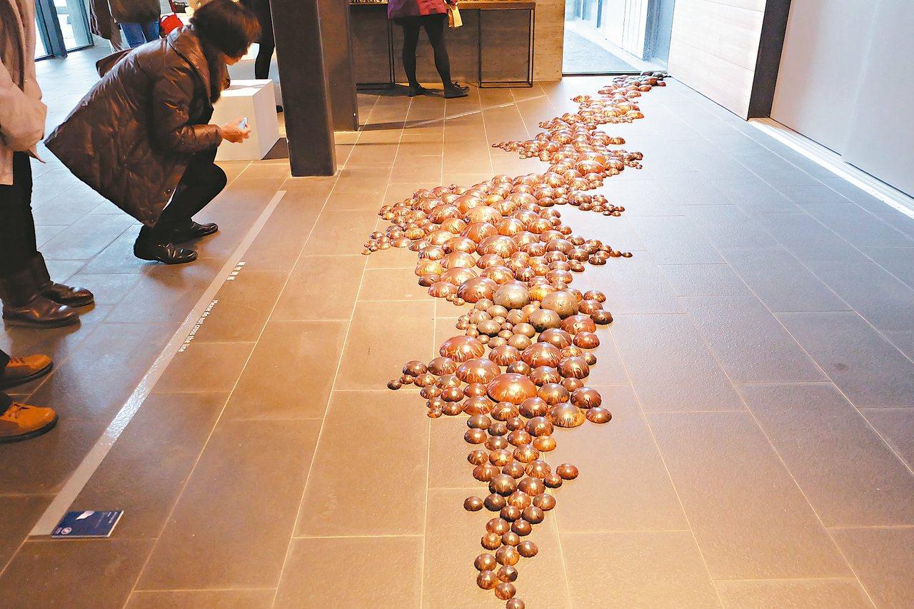 藝術家用紅銅表現輕盈的泡泡,作品大面積平鋪在水泥地面上,視覺上十分震撼,展現視覺...