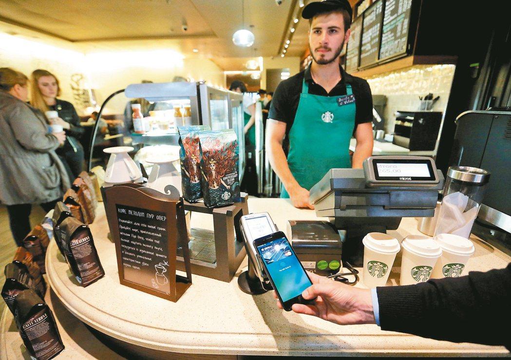 Apple Pay行動支付登台,圖為民眾在莫斯科試用Apple Pay買咖啡。 ...