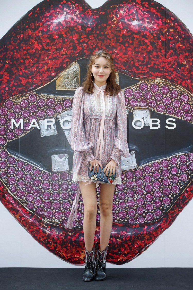 少女時代成員秀英以一襲Marc Jacobs粉紅碎花蕾絲短洋裝出席,手拿俏皮的青...