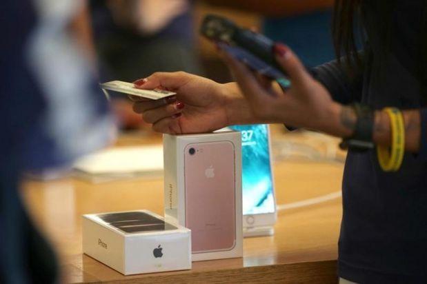 消費者在蘋果商店購買iPhone 7。(圖/路透)