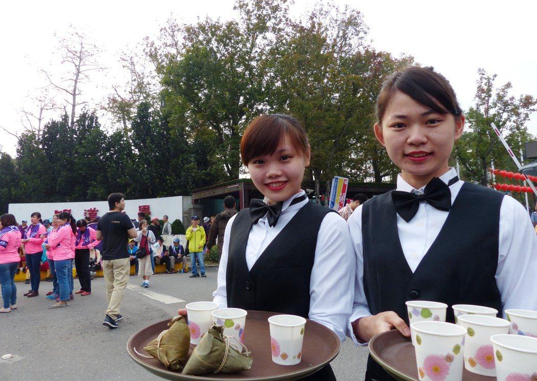 明道大學餐旅系學生在門口送茶水、素粽讓香客止渴、止飢。 記者凌筠婷/攝影