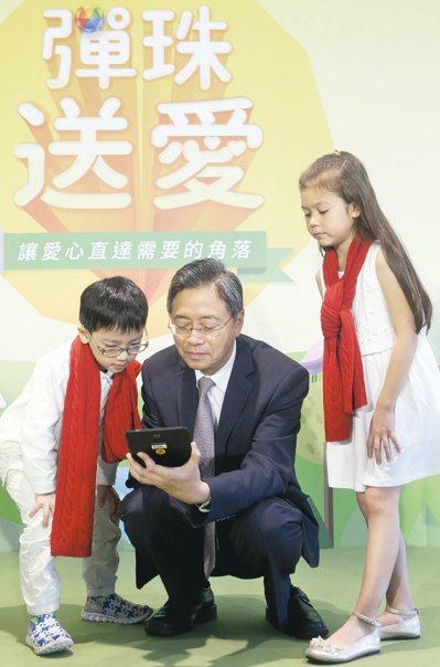 張善政還蹲下和小朋友玩線上版的「彈珠送愛」,當場捐出5元。 記者屠惠剛/攝影