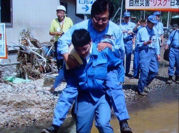 務台俊介遭控視察岩泉町乙茂地區時,由職員背他通過水塘,引發爭議。 圖/取自推特