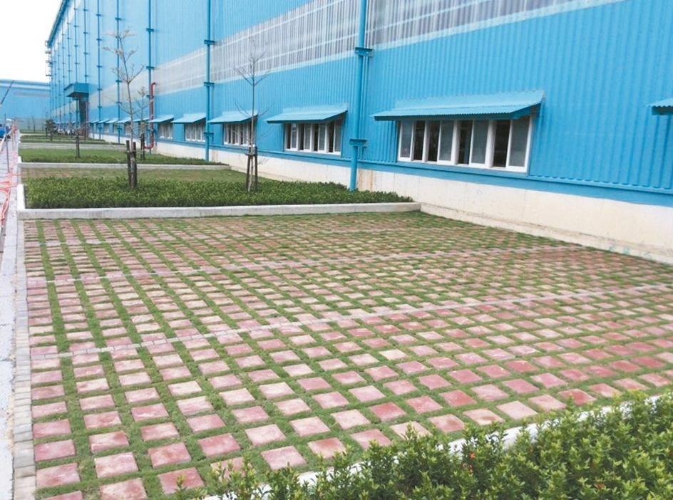 中鋼集團廠內鋪設改質人造石植草磚,鋪設後半年內綠草已生長茂密,與紅色植草磚構成美...