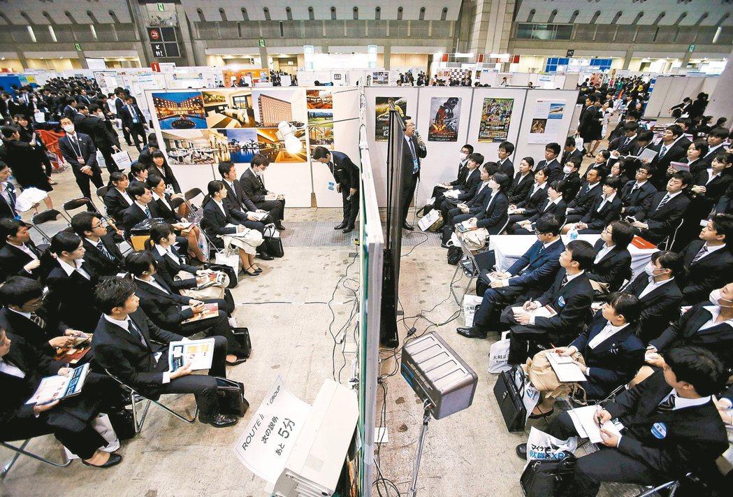 日本畢業生在的東京就博會場,聆聽解說。 路透