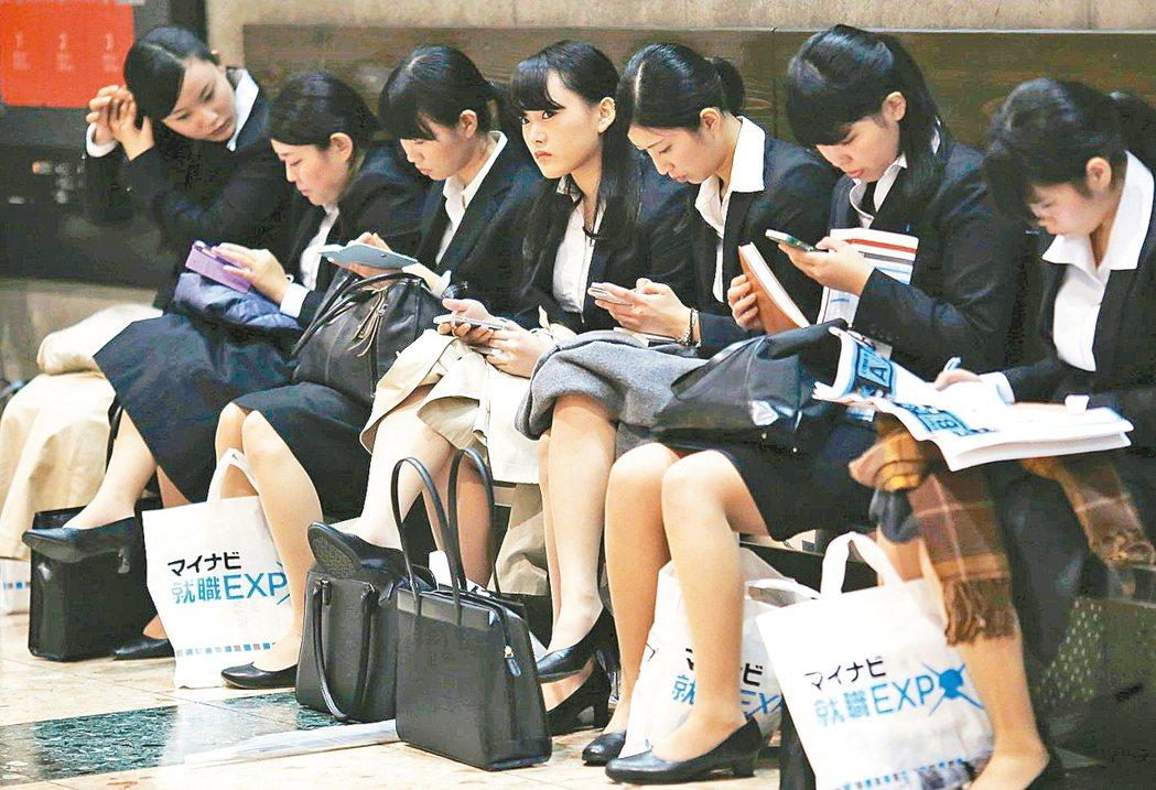 求職者在等待期間滑手機,夾頭髮整理儀容。 路透