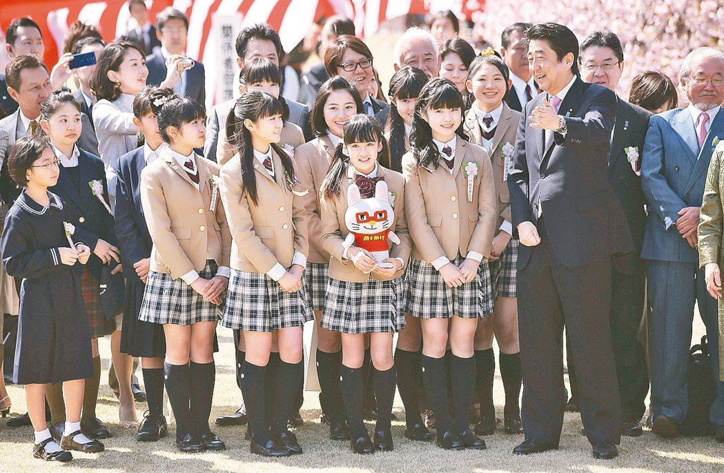 日首安倍晉三(右)和一群女學生在東京新宿御苑賞櫻。 美聯社