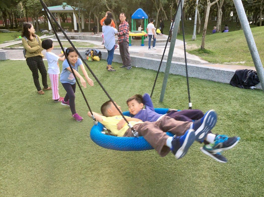 南港區中研公園遊戲場的圓盤型盪鞦韆,一次可以乘載3、4個小朋友,身障孩童也能使用...