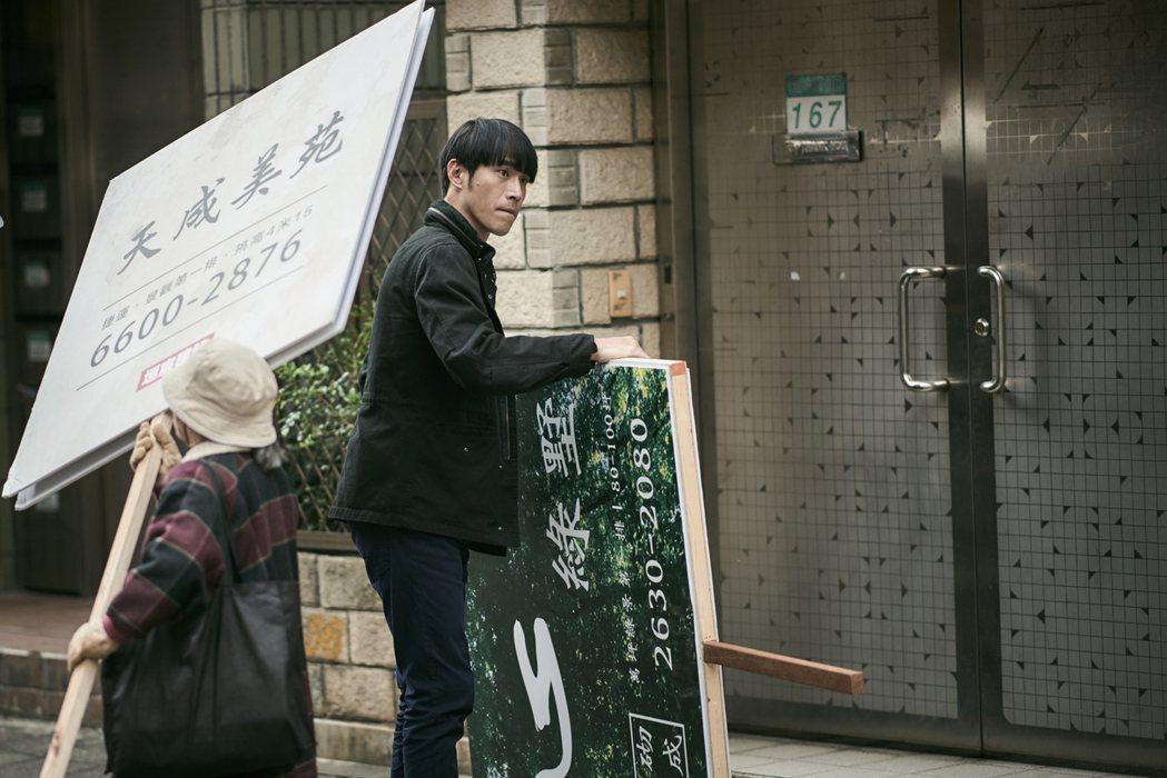黃騰浩演出「勞動之王」體驗當舉牌工。圖/客台提供